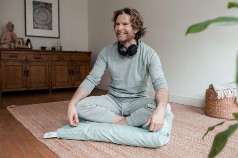 Easz meditation pillow with meditating model.